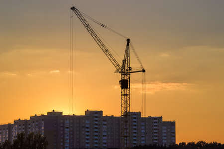 latticed: Tower crane with latticed boom against the background of the sky and a multistory residential building during sunset