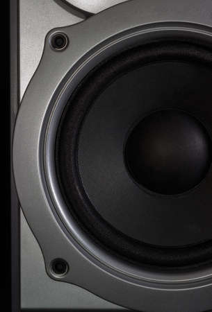 woofer: Fragment of a woofer of a home loudspeaker in silvery housing closeup on the dark background Stock Photo