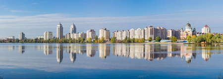 Panorama of modern housing estate on the banks of the bay of the river and building, reflecting in the water in autumn morning