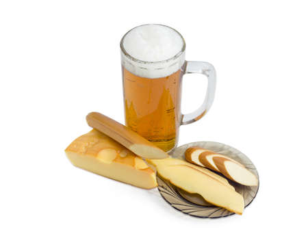 hard cheese: Beer glass with lager beer, piece of a smoked hard cheese, stick of smoked processed cheese and slices of the same smoked cheeses on a saucer on a light background
