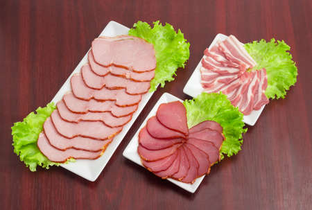 Sliced cured pork tenderloin, smoked pork loin and bacon on a lettuce leaves on the three rectangular white dishes on a dark wooden surface  Stock Photo