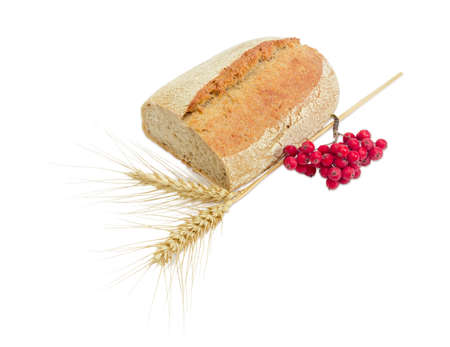 Partially cut wheat sourdough bread, sprinkled with sesame seeds, two spikes of ripe wheat, cluster of red rowan on a light background Stock Photo