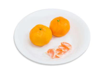 mandarin orange: Two whole fresh ripe mandarin orange and several segments of peeled mandarin orange on a white dish on a light background