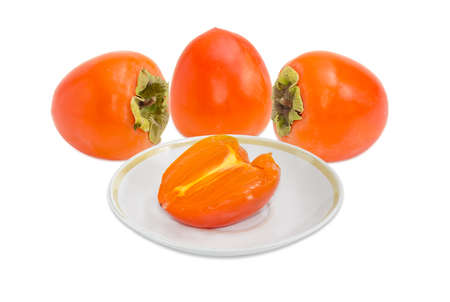 Three whole ripe fresh persimmons and one half of a persimmon on saucer on a light background