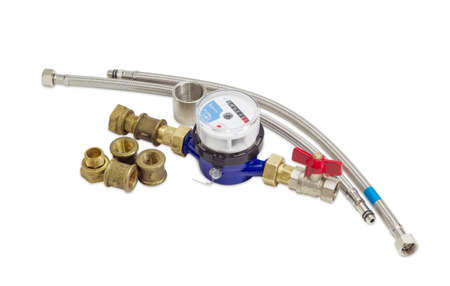 Residential mechanical water meter for consumption measuring of a cold water with some plumbing components on a light background Stock Photo