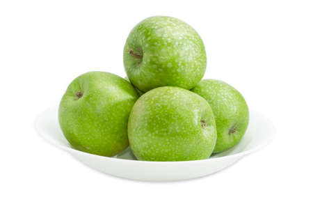 sappy: Several green ripe apples on a white dish on a light background closeup Stock Photo