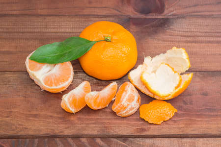sectioned: One fresh whole mandarin orange with leaf and one peeled and sectioned mandarin orange on a dark wooden surface