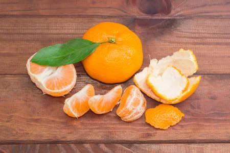 mandarin orange: One fresh whole mandarin orange with leaf and one peeled and sectioned mandarin orange on a dark wooden surface