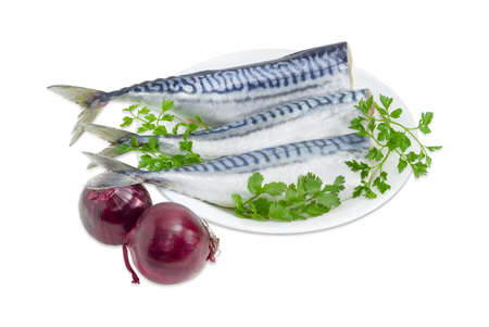 Three carcass of a gutted headless uncooked atlantic mackerel and twigs of parsley and coriander on a white dish and red onions on a light background
