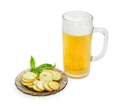 gressins: Beer glassware with lager beer, rusks with basil and pesto sauce flavor and twig of basil on a saucer on a light background