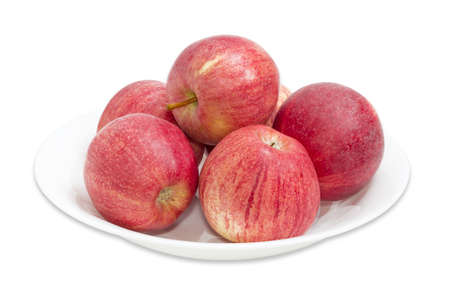 sappy: Several red ripe apples on a white dish on a light background closeup
