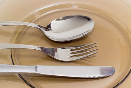 eating utensils: Eating utensils consisting of spoon, fork and knife made from stainless steel on a dark glass dish closeup
