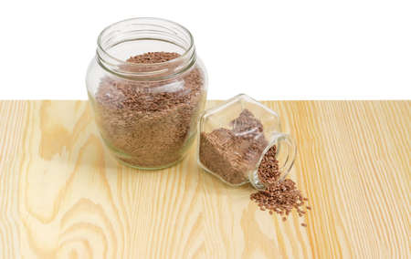 common flax: Brown flax seeds in two different glass jars and partly poured out to the light wooden surface on a light background