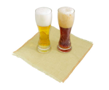 One beer glass lager beer and one beer glass dark beer with foam on a hessian table mat on a light background