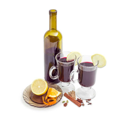 orange peel clove: Mulled wine in two glass mugs with slices of lemon, bottle of red wine and mulling spices for cooking of mulled wine on a light background Stock Photo