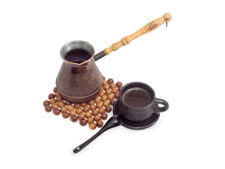 enebro: Recién café negro turco en una vieja cafetera de cobre en el salvamanteles, hecho de bolas de madera de enebro y en la copa de cerámica negro sobre un fondo claro Foto de archivo
