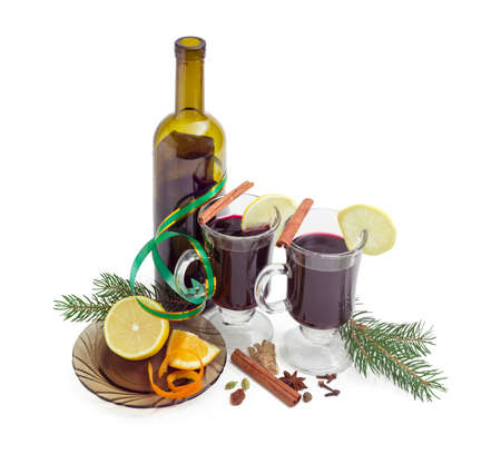 Mulled wine in two glass mugs with slices of lemon, bottle of red wine, mulling spices for cooking of mulled wine and two fir branches on a light background