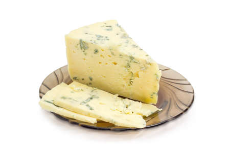 Partly sliced crumbly blue cheese made of sheep milk on a dark glass saucer on a light background