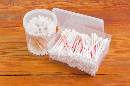 aural: Cotton swabs on a plastic rods in rectangular plastic container and cotton swabs on a wooden rods in round plastic container on an old wooden planks