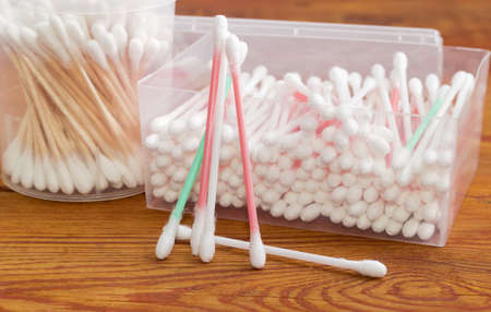 aural: Several cotton swabs on a plastic rods separately and two different plastic containers with different cotton swabs on an old wooden planks closeup
