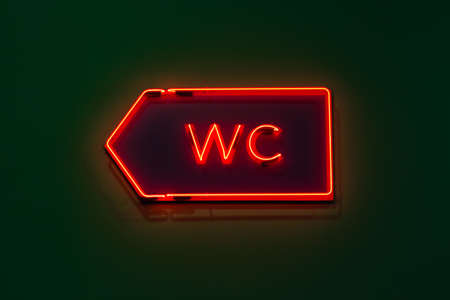 public building: Luminous red neon pointer to the WC on a dark green wall in a public building