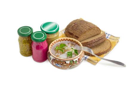 horseradish sauce: Pork aspic in ceramic bowl, brown bread, fork, beet horseradish sauce, mustard, French mustard in small glass jars on a light background Stock Photo