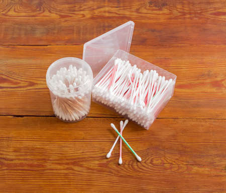 aural: Cotton swabs on a plastic rods in rectangular plastic container, cotton swabs on a wooden rods in round plastic container and several cotton buds separately on old wooden planks