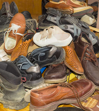 shoestrings: Piled up a bunch of old different worn mens and womens footwear for different seasons