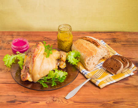 Baked ham hock with lettuce and parsley on a glass dish, beet horseradish sauce, French mustard in small glass jars, fork and different bread on a napkin on a surface of old wooden planks