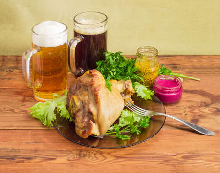 horseradish sauce: Baked ham hock with lettuce and parsley on a glass dish, two glasses of lager beer and dark beer, beet horseradish sauce, French mustard, fork on an old wooden surface