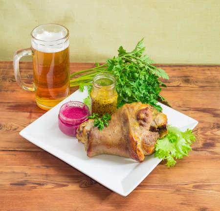 horseradish sauce: Baked ham hock with lettuce and parsley, beet horseradish sauce, French mustard  on a square white dish, glass of lager beer on an old wooden surface