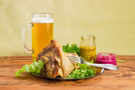 Baked ham hock with lettuce and parsley on a glass dish, glass of lager beer, beet horseradish sauce, French mustard, fork on an old wooden surface  Stock Photo