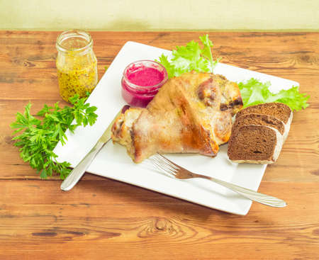 horseradish sauce: Baked ham hock with bunch of parsley and lettuce and bread on a square white dish, beet horseradish sauce and French mustard, knife and fork on a surface of old wooden planks