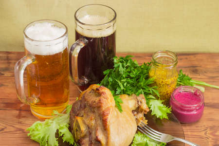 horseradish sauce: Baked ham hock with lettuce and parsley on a glass dish, two glasses of lager beer and dark beer, beet horseradish sauce, French mustard, fork on an old wooden surface  Stock Photo