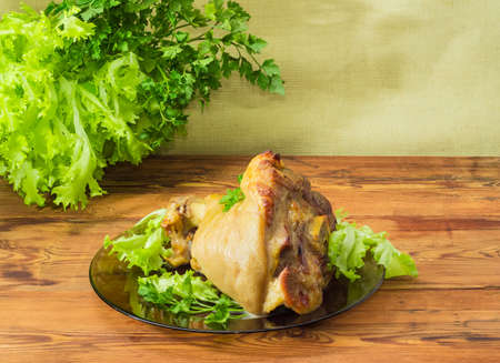 Baked ham hock on a glass dish on the background of parsley and lettuce on an old wooden surface
