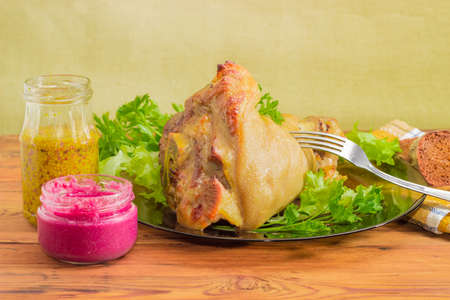 horseradish sauce: Baked ham hock with fork on a glass dish, beet horseradish sauce and French mustard in small glass jars closeup on a surface of old wooden planks  Stock Photo