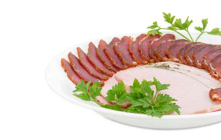 Fragmento de plato blanco con lomo de cerdo seco en rodajas, jamón y ramitas de perejil closeup sobre un fondo claro Foto de archivo