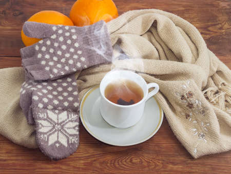 Cup of black tea on a background of womens woolen hybrid mittens and knitted scarf and oranges on wooden surface