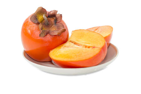 One whole ripe fresh persimmons and one cut in half of a persimmon on saucer on a light background