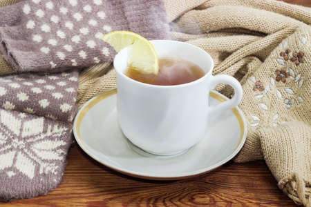 White cup of black tea with lemon on a background of womens woolen hybrid mittens and knitted scarf closeup Stock Photo
