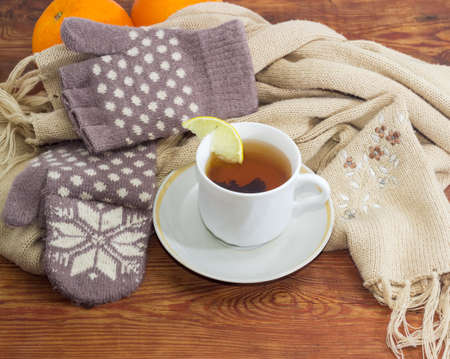 Cup of black tea with lemon on a background of womens woolen hybrid mittens and thick knitted scarf on wooden surface