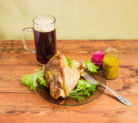 horseradish sauce: Baked ham hock with lettuce and parsley on a glass dish, glass of dark beer, beet horseradish sauce, French mustard and fork on a surface of old wooden planks  Stock Photo