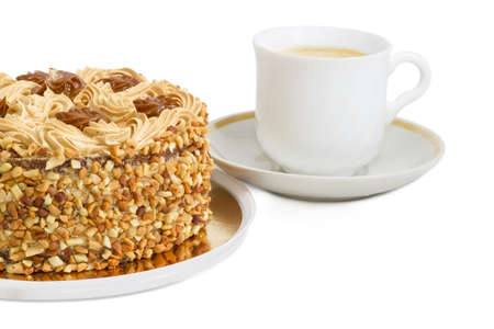 butter icing: Fragment of a round sponge cake, decorated with butter cream and caramelized condensed milk, sprinkled with grated nuts on a background of white cup with coffee with cream on a light background  Stock Photo