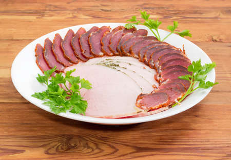 Sliced dried pork tenderloin and ham with twigs of parsley on a white dish on a wooden surface