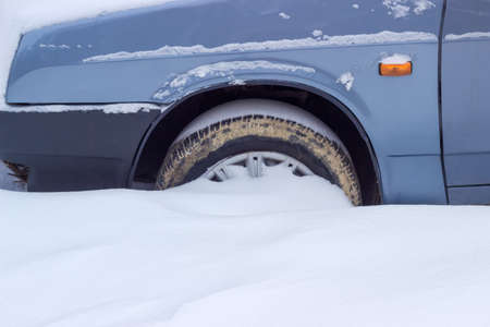 pneumatic tyres: Fragment of the snow covered blue car with a front wheel tire covered with mud  Stock Photo