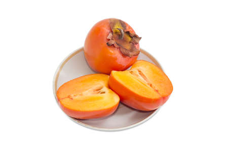 One whole ripe fresh persimmons and one cut in half of a persimmon on saucer on a light background  Stock Photo