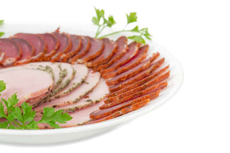 charcutería: Fragment of white dish with sliced dried pork tenderloin, ham and twigs of parsley closeup on a light background