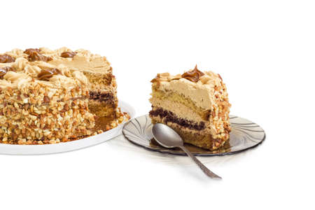 Piece of layered sponge cake, decorated with butter cream, caramelized condensed milk and nuts with spoon on a glass saucer and partly sliced cake on a light background