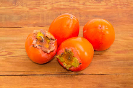 Several ripe fresh persimmons on an old wooden surface
