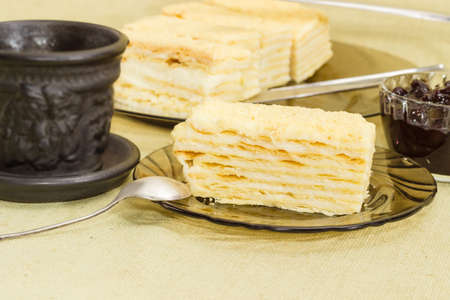 Piece of layered sponge cake on a glass saucer with spoon on the background of the rest of the cake, black cup and jam closeup on a cloth surface